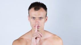 Stående av den stiliga shirtless mannen som visar den tysta gesten, vit bakgrund Royaltyfri Foto