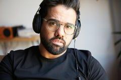Stående av den stiliga skäggiga mannen i hörlurar som hemma lyssnar till musik Koppla av och vilotidbegrepp _ Arkivfoto