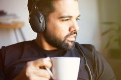 Stående av den stiliga skäggiga mannen i hörlurar som lyssnar till hemmastadd musik och dricker kaffe Koppla av och vilotid Royaltyfria Bilder