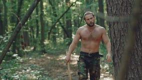 Stående av den stiliga skäggiga mannen med yxa i skogen långsamt stock video