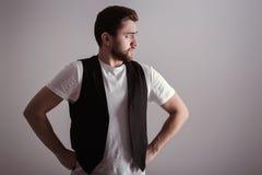 Stående av den stiliga unga allvarliga mannen i den vita skjortan på grå bakgrund Royaltyfri Foto