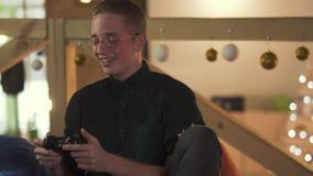 Stående av den stiliga unga manliga arbetaren som har roligt på avbrottet som spelar videospel med utmärkt lynne i modern coworki stock video