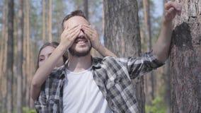 Stående av den stiliga unga mannen i pinjeskogen, flickan som bakifrån täcker hans ögon med närbild för händer enhet arkivfilmer