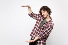 Stående av den stiliga unga mannen i tillfällig kläder som gör en gest visa format med vertikal workspace som isoleras på vit arkivfoto