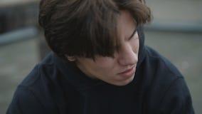 Stående av den stiliga unga mannen med lätta leenden för lägre huvud 4K stock video