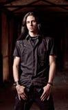 Stående av den stiliga unga mannen med långt hår Arkivfoto