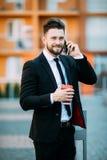 Stående av den stiliga unga mannen som lyckligt ler, medan gå i stadsgator som rymmer smartphone- och papperskaffekoppen arkivfoto