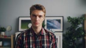 Stående av den stiliga unga mannen som ser kameran med den olyckliga framsidan som bär ljust rutigt skjortaanseende i modernt lager videofilmer