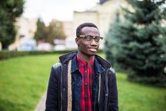 Stående av den stiliga unga mannen som utanför utomhus ler med gatan för påse Fotografering för Bildbyråer