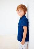 Stående av den stiliga unga pojken, unge som poserar nära den vita väggen royaltyfria bilder