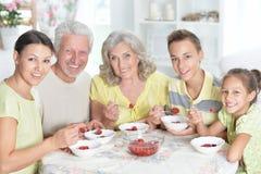 Stående av den stora lyckliga familjen som äter nya jordgubbar arkivfoton