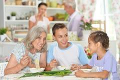 Stående av den stora lyckliga familjen som har frukosten arkivfoto