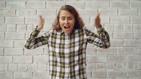 Stående av den stressade unga kvinnan som skriker och gör en gest uttrycka negativa sinnesrörelser som går därefter bort förargat arkivfilmer