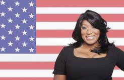 Stående av den tillfälliga kvinnan för blandat lopp mot amerikanska flaggan fotografering för bildbyråer