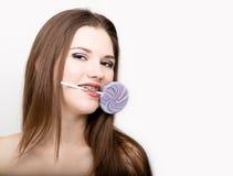 Stående av den tonåriga flickan som visar tand- hänglsen och den hållande godisen Arkivbild