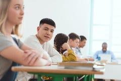 Stående av den tonårs- asiatiska studenten för högstadium med klasskompisar och att sitta för lärare arkivfoton