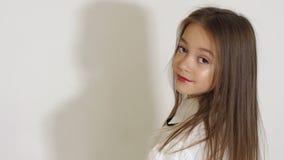 Stående av den tonårs- flickan med långt hår i studio på vit bakgrund arkivfilmer