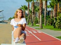 Stående av den tonårs- flickan, medan sitta på den vita bänken Arkivfoton