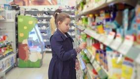 Stående av den tonårs- flickan som stjäler livsmedel i ett stort lager lager videofilmer
