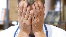 Stående av den trötta doktorn, framsida som täckas med handen royaltyfria foton