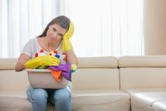 Stående av den trötta kvinnan med korgen av lokalvårdtillförsel som hemma sitter på soffan Arkivbild