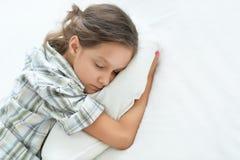 Stående av den trötta lilla flickan som sover i säng royaltyfri foto