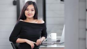 Stående av den trendiga unga asiatiska affärskvinnan som tycker om avbrottet som sitter på tabellen som ser kameran stock video