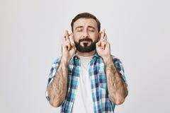 Stående av den typiska vuxna europeiska mannen med skägget och mustaschen i kontrollerad skjorta som korsar fingrar och att uttry royaltyfria bilder