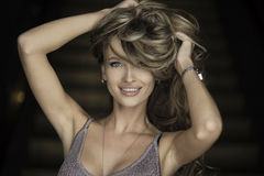 Stående av den underbara unga blonda kvinnan med långt hår som ser kameran som ler Royaltyfri Fotografi