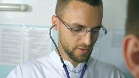 Stående av den undersökande patienten för stilig doktor med stetoskopet Ungt lyssnande hjärtslag för medicinsk arbetare av sjukt stock video