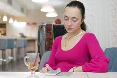 Stående av den unga affärskvinnabruksmobiltelefonen, medan sitta i bekväm coffee shop under arbetsavbrott, Fotografering för Bildbyråer