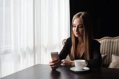 Stående av den unga affärskvinnabruksmobiltelefonen, medan sitta i bekväm coffee shop under arbetsavbrott royaltyfria foton