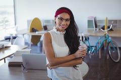 Stående av den unga affärskvinnainnehavdrinken på kontoret royaltyfria bilder