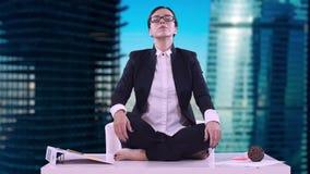 Stående av den unga affärskvinnan i kontoret Hon satt på skrivbordet i den Lotus positionen och att meditera i en affär arkivfilmer