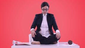 Stående av den unga affärskvinnan i kontoret Hon satt på skrivbordet i den Lotus positionen och att meditera i en affär lager videofilmer