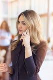Stående av den unga affärskvinnan i regeringsställning som rymmer hennes mobil royaltyfri fotografi