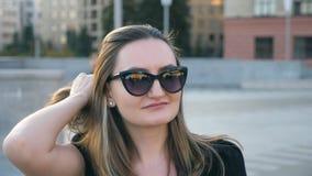 Stående av den unga affärskvinnan i solglasögon med cityscape på bakgrund Lycklig attraktiv affärskvinna som ser lager videofilmer