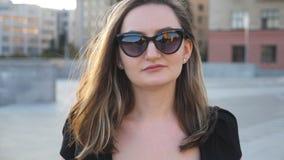 Stående av den unga affärskvinnan i solglasögon som går i stadsgata Attraktiv affärskvinna som ser kameran Vända mot stock video
