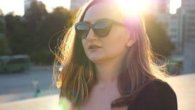 Stående av den unga affärskvinnan i solglasögon som går i stadsgata med solsignalljuset på bakgrund Framsida av attraktivt arkivfilmer