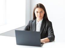Stående av den unga affärskvinnan med bärbara datorn i det offic Royaltyfri Fotografi