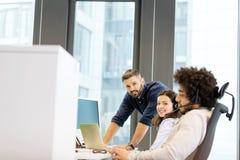 Stående av den unga affärskvinnan med manliga kollegor som i regeringsställning arbetar Arkivfoton