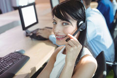 Stående av den unga affärskvinnan som använder hörlurar med mikrofon Royaltyfria Bilder