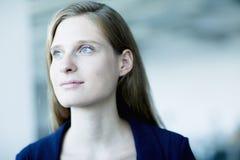 Stående av den unga affärskvinnan som ser bort i begrundande arkivfoton