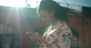 Stående av den unga afrikansk amerikankvinnan som använder telefonen, utomhus Royaltyfri Fotografi