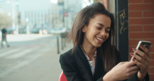 Stående av den unga afrikansk amerikankvinnan som använder telefonen, utomhus Arkivbild