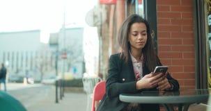 Stående av den unga afrikansk amerikankvinnan som använder telefonen, utomhus Arkivfoto
