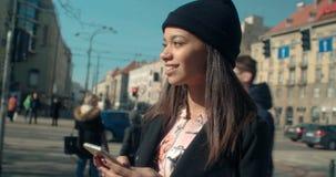 Stående av den unga afrikansk amerikankvinnan som använder telefonen, utomhus Royaltyfri Foto