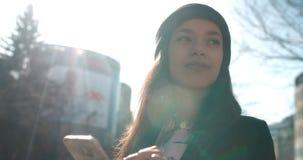 Stående av den unga afrikansk amerikankvinnan som använder telefonen, utomhus Fotografering för Bildbyråer