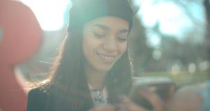 Stående av den unga afrikansk amerikankvinnan som använder telefonen, utomhus Royaltyfria Bilder