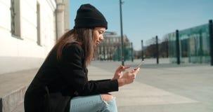 Stående av den unga afrikansk amerikankvinnan som använder telefonen, utomhus Arkivfoton